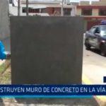 Construyen muro de concreto en la vía pública